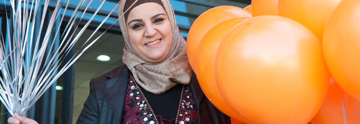 A smiling woman in headdress with bunches of orange balloons