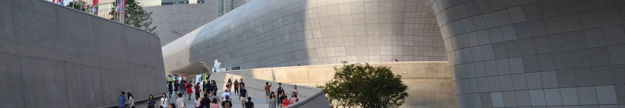 Building with curved walls and people on walkway